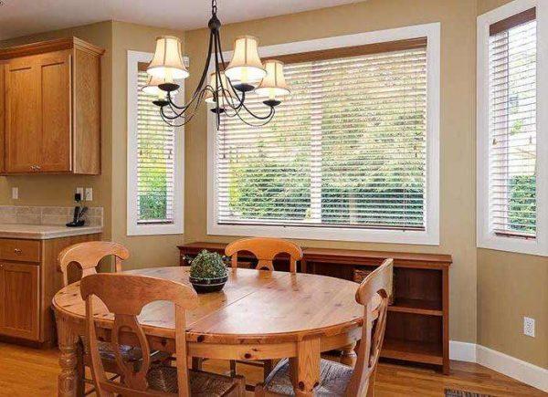 круглый стол и люстра на кухне с эркером