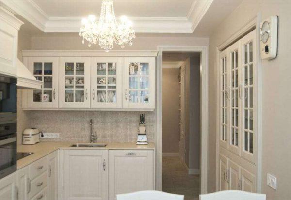 светлый интерьер кухни с хрустальной люстрой
