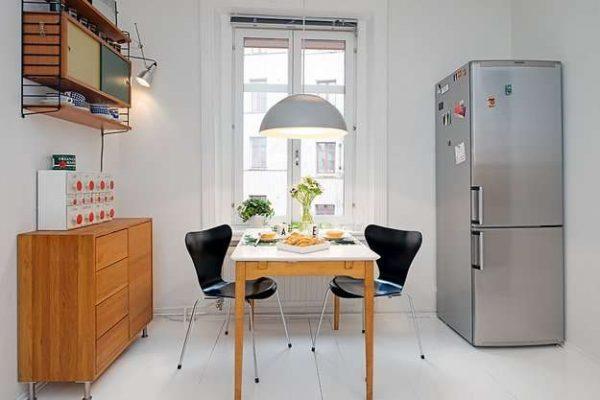 металлический холодильник на маленькой кухне у окна