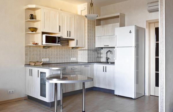 холодильник у дверей маленькой кухни