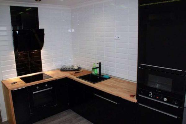 чёрная кухня без верхних шкафов с деревянной столешницей