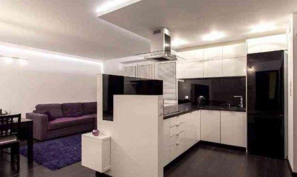 белый гарнитур с чёрной столешницей на совмещённой кухне с залом