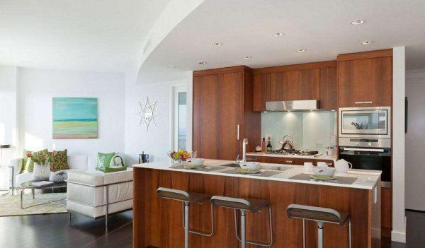 кухонный гарнитур из дерева с островной рабочей зоной на кухне совмещённой с залом