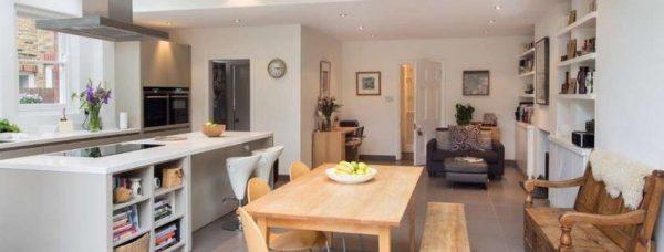 кухня совмещённая с гостиной в частном доме с деревянной лавкой и обеденным столом