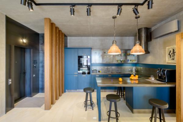 синий гарнитур и деревянные колоны на кухне
