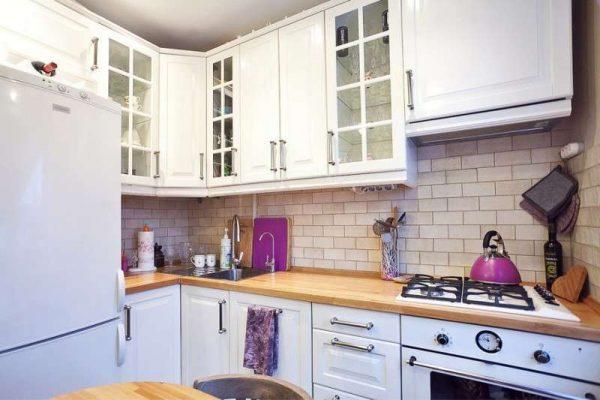 белый угловой гарнитур на маленькой кухне