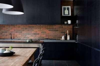 чёрная кухня с кирпичной стеной