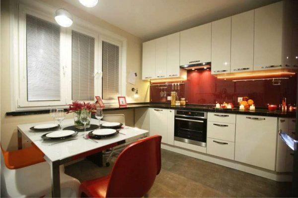 белый гарнитур с красным фартуком в интерьере кухни