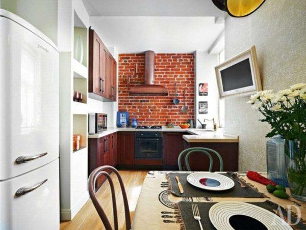 тёмно красный гарнитур в интерьере кухни с кирпичной стеной