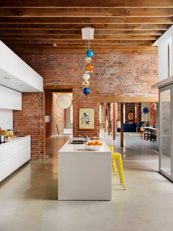 кирпичные стены и деревянные балки на потолке кухни лофт